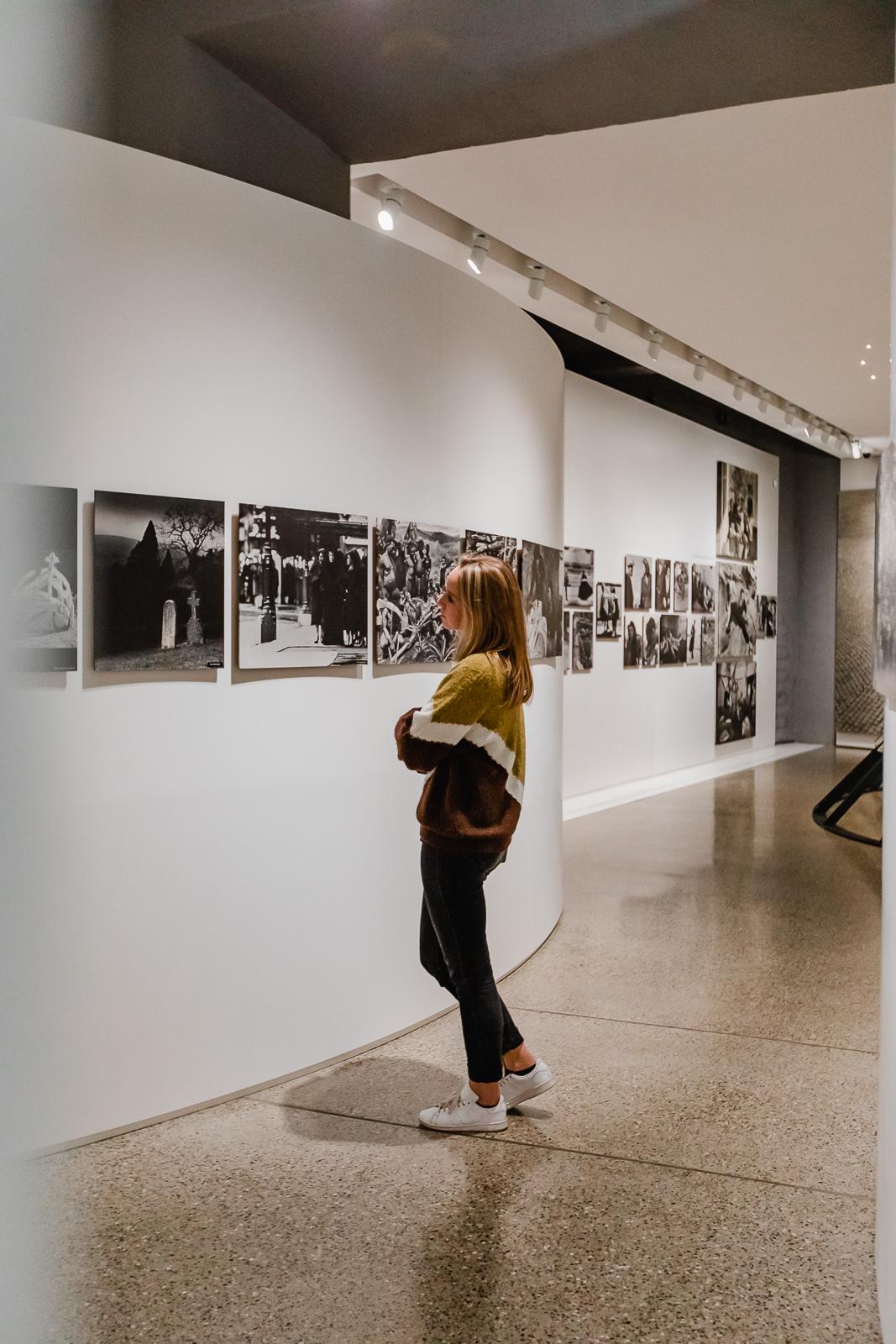 Girl looking at photos at family of man