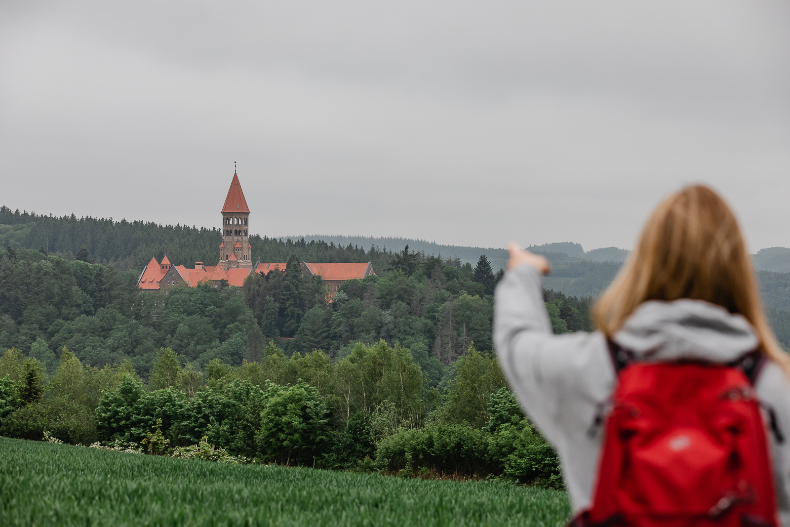Girl red backpack view of Clervaux abbey