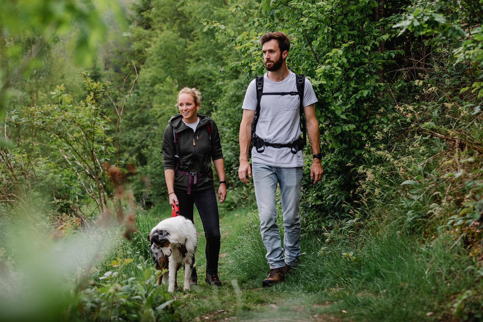 Couple and australian sheperd walking in forest
