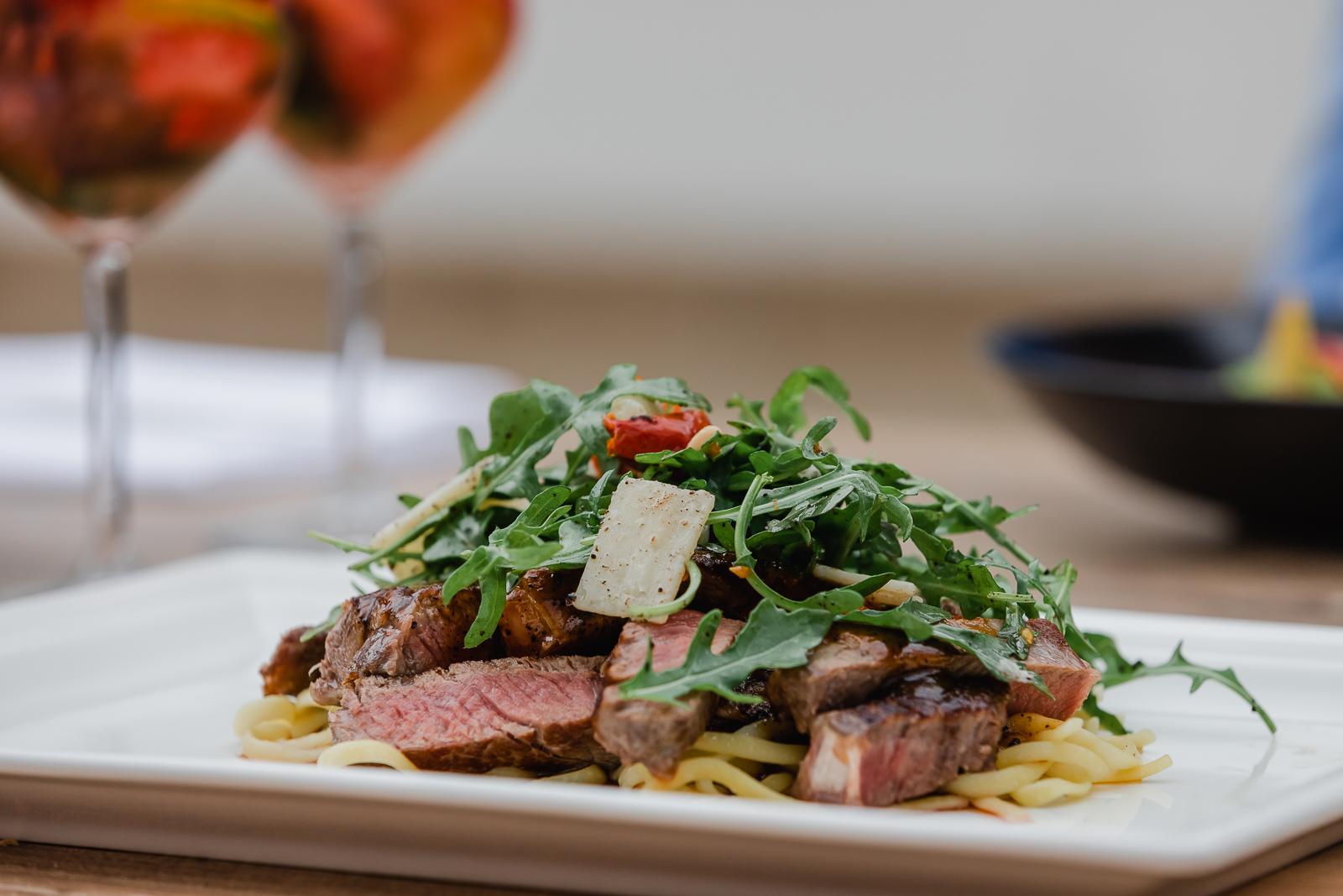 Plate of tagliatelli with steak and rucola